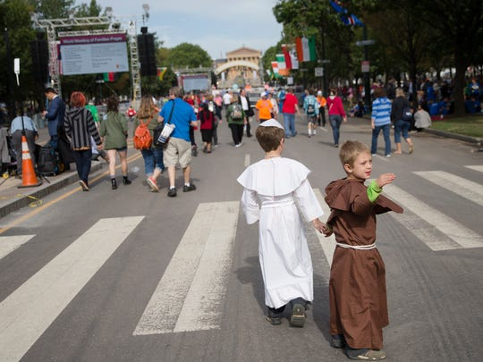 Steve Schuette, right, dressed as St. Francis, is lead by the hand of brother John Paul, who is dressed as Pope Francis, as they walk along Benjamin Franklin Parkway, Sunday, Sept. 27, 2015, in Philadelphia. Pope Francis will end the final day of his three-city U.S. tour with a Mass on Philadelphia's grandest boulevard. (AP Photo/John Minchillo)