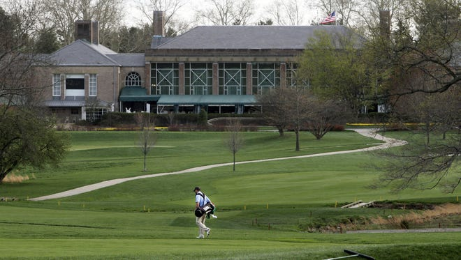 A golfer walks the greens at the DuPont Country Club. The club was offered for sale last week.