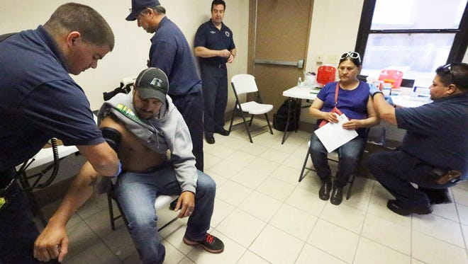 El Paso firefighter John Gallegos, left, applies a blood pressure monitor to Ricardo Dominguez while firefighter paramedic Albert Romero, far right, administers a flu shot to Reyna Garcia at the Fire Department's Safety Health Outreach Center at 5415 Trowbridge Drive. The Fire Department and the El Paso health department collaborate in the Vaccinations for Health program in which they provide influenza and pneumonia vaccines, blood pressure and glucose screening and colorectal screening kits free to residents of El Paso and Hudspeth counties who are age 18 and older and lack medical insurance or are enrolled in Medicaid.