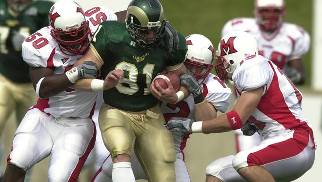 Colorado State University's Joel Dreessen (81) is brought down by Miami RedHawks Phil Smith (50), Matt Pusateri (19) and John Busing (12) during the first half of the game September 20, 2003 at Hughes Stadium.