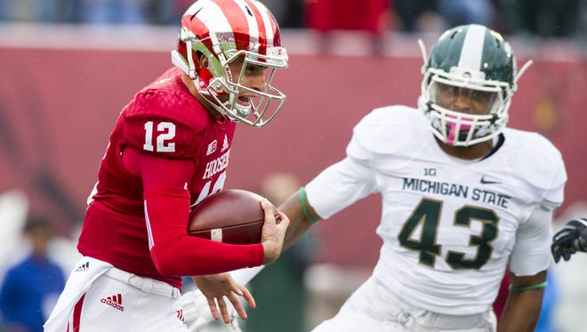 Indiana University freshman Zander Diamont (12) rushes the ball into the Michigan State defense on the first play from scrimmage during the first half of action. Indiana University hosted Michigan State University in Big Ten football action, Saturday, October 18, 2014, in Bloomington, Ind.