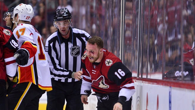 Dec 8, 2016: NHL linesman Brian Mach (78) escorts a bloody Arizona Coyotes left wing Max Domi (16) after a fight in the third period against the Calgary Flames at Gila River Arena.
