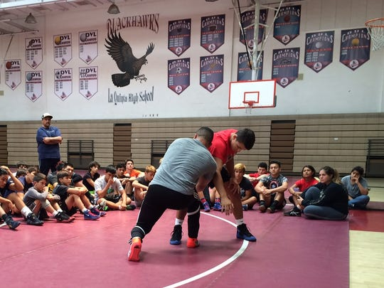 Campers watch at La Quinta High School as two-time NCAA champion Chris Pendleton shows some moves Friday.