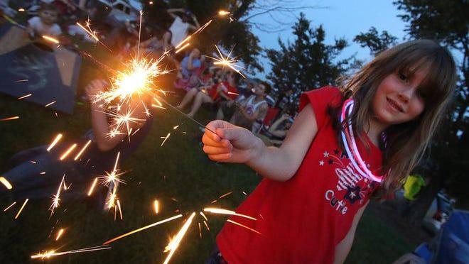 Six-year-old Elizabeth Gustashaw enjoys a sparkler prior to the start of the big fireworks display July 4, 2016.