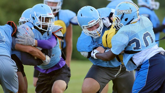 Football players run plays during a past practice at Burns High School.