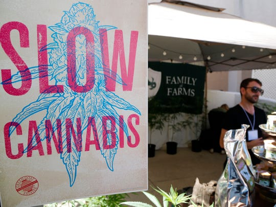 "A banner for ""Slow Cannabis"" is displayed at the Emerald Exchange stand at ""The State of Cannabis,"" a California industry group meeting in Long Beach on Thursday. California's emerging marijuana industry is being rattled by an array of unknowns as the state races to issue its first licenses to grow and sell legal recreational pot on Jan. 1."