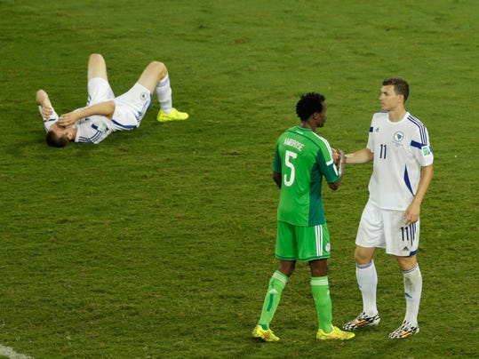 Bosnia's Edin Dzeko shakes hand with Nigeria's Efe Ambrose as Bosnia's goalkeeper Asmir Avdukic sits on the floor during the group F World Cup soccer match between Nigeria and Bosnia at the Arena Pantanal in Cuiaba, Brazil, Saturday, June 21, 2014. (AP Photo/Fernando Llano)