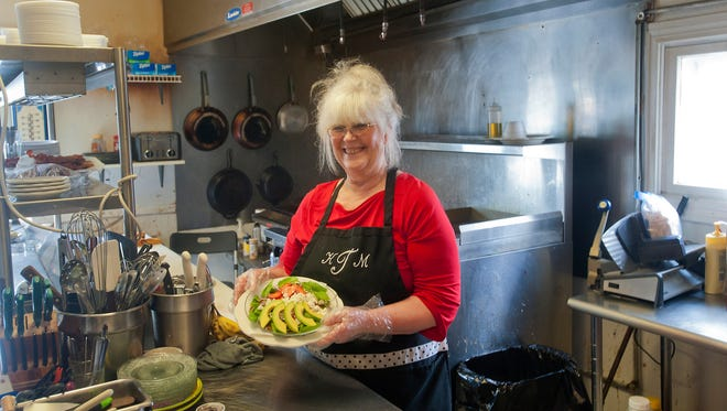 Kathy Thomas, chef and co-owner of Cafe At Main Street, in Jeffersontown, holds her Spicy Spring Salad.