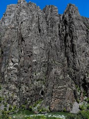 Cliff walls towers above the Gunnison River as it flows through Black Canyon, Monday, June 22, 2015.