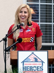 NHRA drag racer Courtney Force speaks during a ceremony Wednesday June 13, 2018 in Navarre, Florida in which widow Natasha De Alencar and her children received a new home through the Building Homes for Heroes non-profit organization. De Alencar's husband, U.S. Army Special Forces Staff Sgt. Mark De Alencar, died April 8, 2017 while serving in Afghanistan. Force was there representing Advance Auto Parts, one of the sponsors of Building Homes for Heroes. (Devon Ravine/Northwest Florida Daily News via AP)