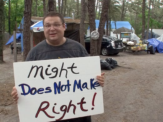 Lakewood Tent City resident Alex Libman walks through the community Friday, May 30, 2014. with a protest sign.  The township intends to close the encampment on Sunday.   STAFF PHOTO