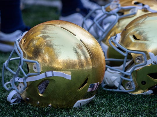 Notre Dame players are reflected in a helmet as they sing the alma mater following the win at Notre Dame Stadium.