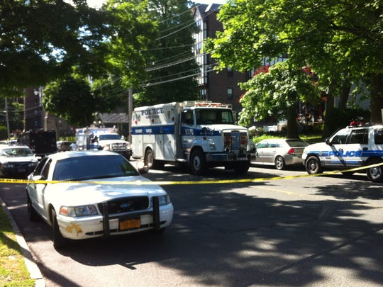 Police vehicles on the corner of Lorraine Avenue and East Lincoln Avenue in Mount Vernon Friday, June 6, 2014, as police conduct a manhunt for Leroi Bouche, who authorities said struck a drug investigator with a car.