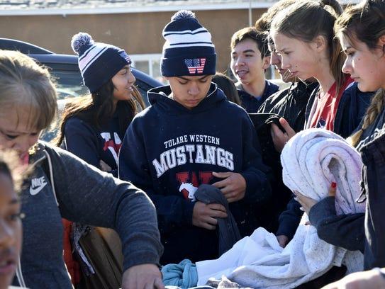 Tulare Western freshman Blake Beltran organizes sweatshirts