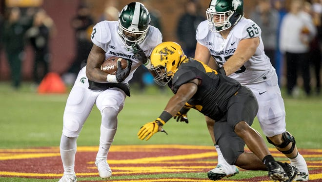 Michigan State running back LJ Scott rushed for 194 yards last week at Minnesota, behind the push of Brian Allen, right, and the Spartans offensive line.