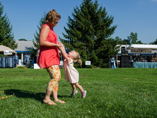 Charlotte Heit, 2, of Lake Orion, plays with her mom, Aimee Heit, Sunday, Sept. 4, during the BlueChiliGrass Festival at Goodells County Park.