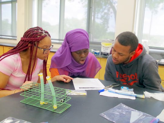 From left, Tailor Davis, Binti Mohamad and De'aunte Johnson prepare the science experiment they sent into space.