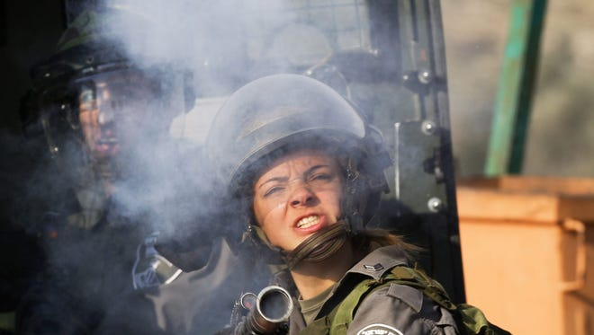 A female Israeli soldier fires tear gas on Palestinian protesters from Jalazoun Refugee camp, north of Ramallah in the West Bank as they clash with Israeli soldiers during a protest Feb. 7, 2014, near Bet El.