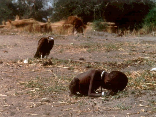 FILE--This photograph by free-lance South African photographer Kevin Carter won the Pulitzer prize for feature photography for The New York Times, it was announced Tuesday, April 12, 1994 by Columbia University. A vulture hovers over a starving Sudanese girl who had collapsed on her way to a feeding center, in this photo published March 26, 1993.