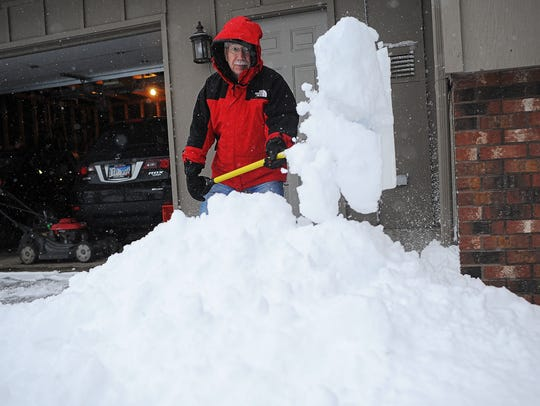 Jim Paulson, of Sioux Falls, shovels part of his driveway