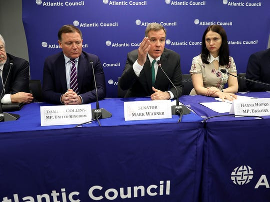 U.S. Sen. Mark Warner, D-Va., (center) is joined by, from left, Latvian Parliament member Ojars Kalnins, United Kingdom Parliament member Damian Collins, Ukrainian Parliament member Hanna Hopko and Czech Republic Parliament member Jan Lipavsky for a news conference at the Atlantic Council July 16, 2018, in Washington, D.C.