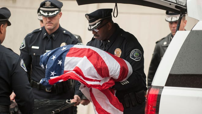 Camden County Police Lt. Zsakhiem James, center,  places the body of his longtime partner Officer Zero on a gurney at the Rothman Animal Hospital in Collingswood after an procession in honor of Officer Zero on Tuesday.  Officer Zero, a veteran K-9 officer who was Camden's first police dog, passed away early Tuesday morning at his home.  12.29.15