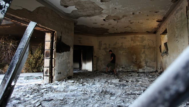 A Libyan man walks in the rubble of the damaged  U.S. facility in Benghazi, Libya, after an attack that killed four Americans, including Ambassador Chris Stevens on the night of Tuesday, Sept. 11, 2012.