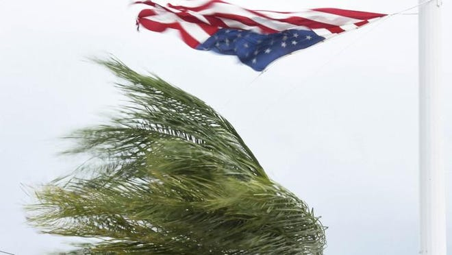 A large flag at a Tequesta wharehouse on Old Dixie blows with the surging winds during Hurricane Irma.