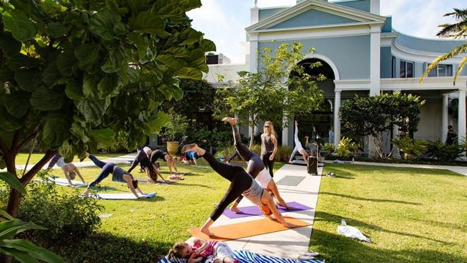 Haute Yoga holds an outdoor class in the courtyard of a revitalized Royal Poinciana Plaza on April 5. Ella Stapleton, 3, plays with a phone while her mother, Maureen Stapleton of Bronxville, N.Y., and her grandmother, Pam Williams of Palm Beach, take part in the free yoga class.