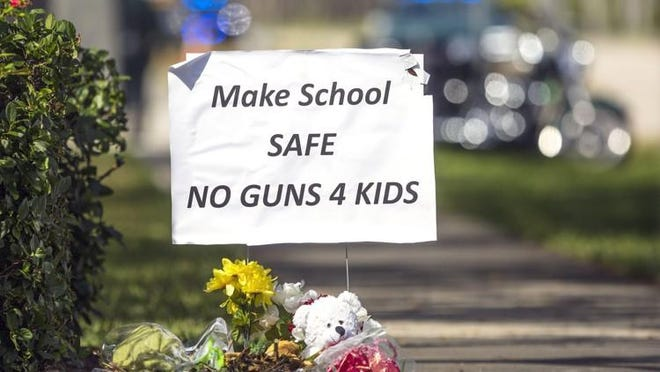 A sign supporting gun control sits down the street from Marjory Stoneman Douglas High School in Parkland as students and their parents arrived Feb. 28.