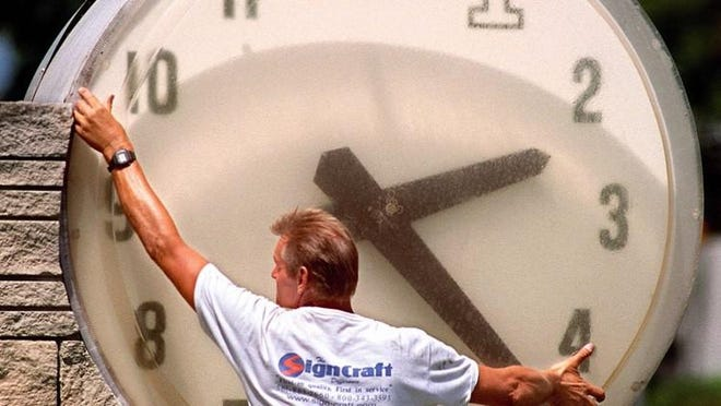 Joe Roskey, of Riviera Beach, updates an outdoor clock in downtown West Palm Beach after the switch to daylight savings time in April 1999.