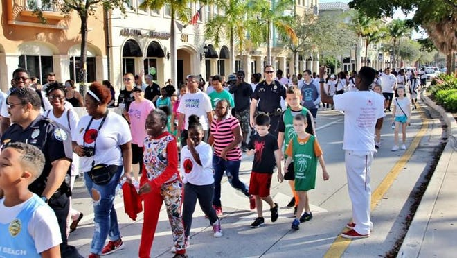 Residents and Delray Beach Police officers march in the 2nd annual Walk Against Violence.