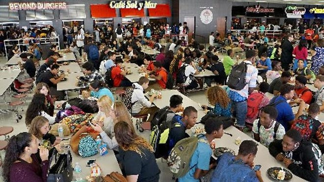 Students sit down to lunch in a Palm Beach County school cafeteria. File photo from 2015.