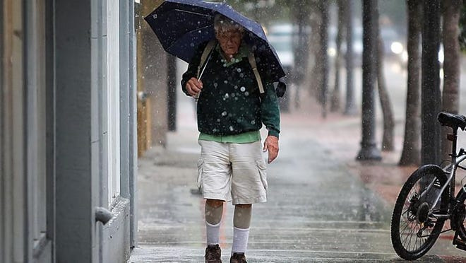 A man walks through a downpour along S. Olive Ave. just south of Clematis St. Wednesday afternoon as rain begins to enter the downtown area May 4, 2016. Damon Higgins / The Palm Beach Post