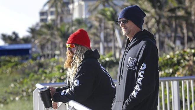 Lake Worth Ocean Rescue lifeguards Mat Botts (left) and Doug Yoakum check out the ocean conditions at Lake Worth Beach for their beach report at the start of a cold day on Dec. 13.