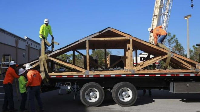 Weitz Co. workers load roof sections of a house made by Seminole Ridge High School construction academy students onto a trailer in Loxahatchee. Six roof sections and four house modules were moved from the school to be assembled later in West Palm Beach.