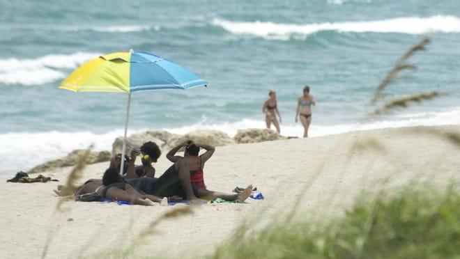 Sunbathers take advantage of sunny weather at Midtown Beach Saturday. Meghan McCarthy / Palm Beach Daily News