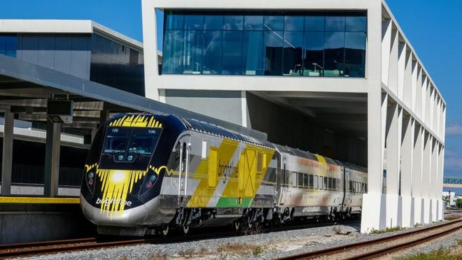 The Brightline BrightOrange train stops at the downtown West Palm Beach station during testing on Dec. 8, 2017.