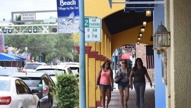 Shoppers stroll along Atlantic Avenue in downtown Delray Beach.