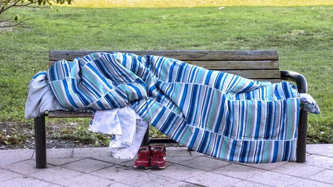 A homeless person slept under a blanket on a bench on Banyan Boulevard at Narcissus Avenue in downtown West Palm Beach.