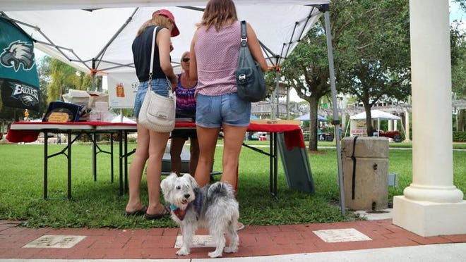 Bailey the dog stands with her owners, Maria and Jessica Goodstein of Wellington, as they talk with baker Pamela Zeitz at the green market at Veterans Park in Royal Palm Beach in 2017. [Palm Beach Post file photo]