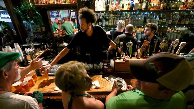 Bartender Matty O'Brien serves the crowd inside O'Shea's Irish Pub during the St. Patrick's Day block party on Clematis Street on March 17, 2016.