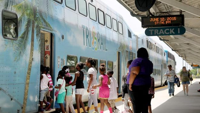 Passengers board the Tri-Rail train at the West Palm Beach station.