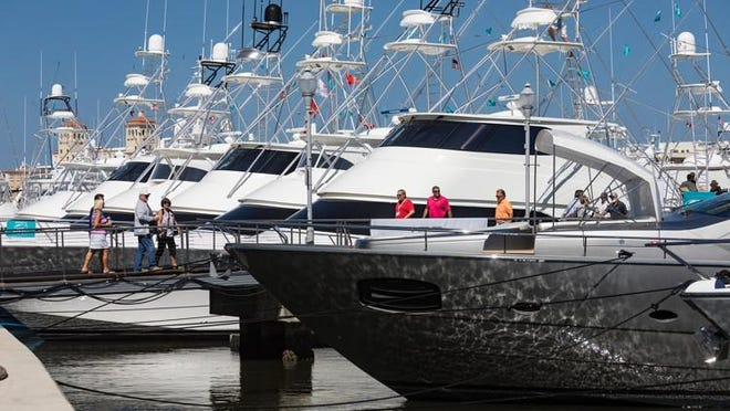 People look at yachts at the Palm Beach International Boat Show in West Palm Beach on March 22, 2018.