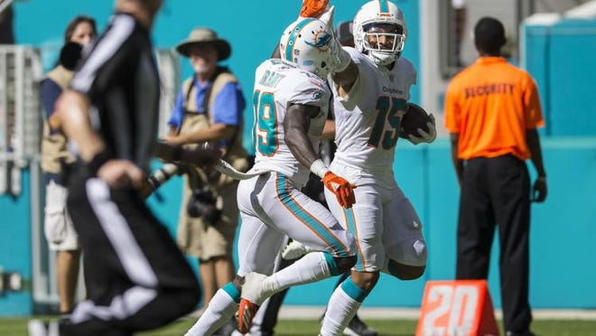 Miami Dolphins wide receiver Albert Wilson (15), high fives Miami Dolphins wide receiver Jakeem Grant (19), on his way to scoring a touchdown against the Oakland Raiders during fourth quarter action of their NFL game Sunday Sept. 23, 2018.
