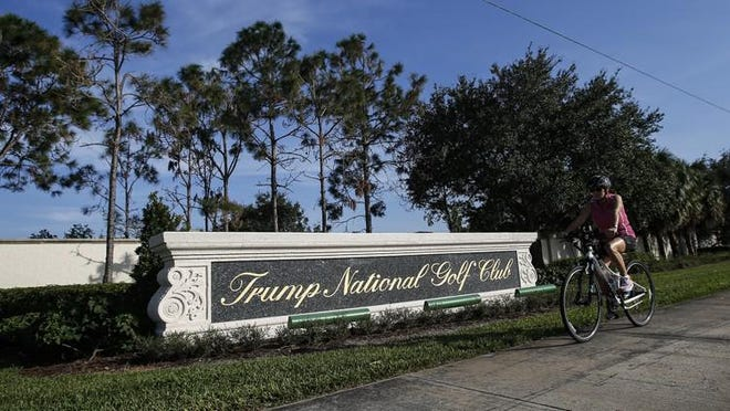 A bike rides by the sign of Trump National Golf Club, November 11, 2016 in Jupiter.