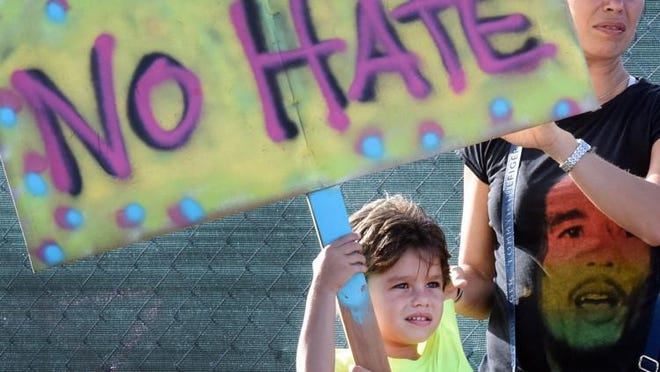 "WEST PALM BEACH -- William Hinkley, 5, of Coral Springs, stands with his mother, Gelena Hinkley, during a ""Rally Against Hate"" protest in 2017 at the corner of Southern Boulevard and Flagler Drivethe protest. His father, Joe Hinkley, brought his five children because he believes it is important to teach them to confront racism and be unafraid to stand up against hatred."