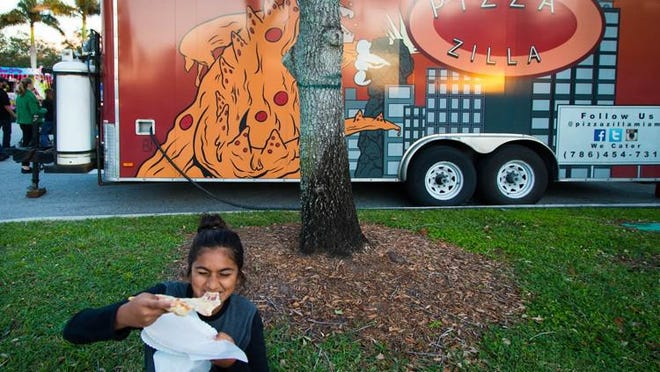 Divya Seedial, of Wellington, bites into a slice of pizza in October 2017 from the Pizza Zilla truck at the food truck invasion in Wellington. Wellington is launching a reimagined, COVID-safe version of its popular weekly food truck events.