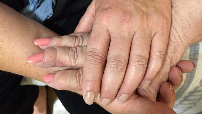 Samantha Forzano holds her mother's hand at Arden Courts of West Palm Beach, a memory care facility that assists seniors with Alzheimer's and dementia.