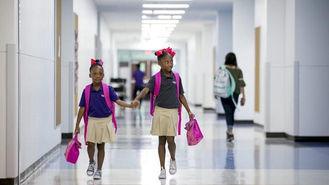 Sisters Coco Simpson, left, and Chloe, arrive for school at Austin Achieve charter school in 2018. Charter school growth in Austin, and statewide, has boomed in recent years. Three charter school operators are seeking state approval to set up in Central Texas.